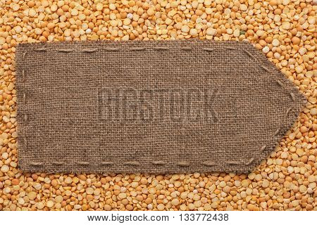 Pointer of burlap lying on a peas background with place for your text