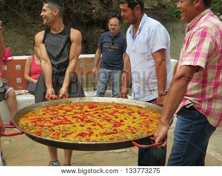 ElChorro Spain May 28 2016: Large cooked paella dish carried by four people at local fiesta in Andalusia.