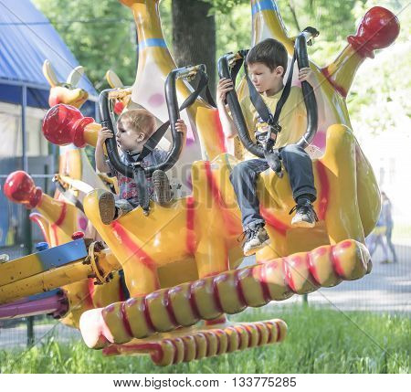 Rostov-on-Don Russia- May 29 2016: Two boys with admiration go for a drive on the carousel in the park named after Ostrovsky