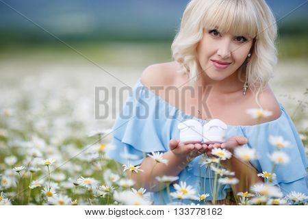 Happy young pregnant woman on a white field of blooming daisies in a mountain area, blonde,with long eyelashes and light make-up,ears are silver earrings,large belly,dressed in a blue sundress,holding in their hands little baby booties white