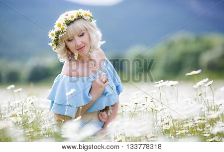 Spring portrait of a pregnant woman on a white field of blooming daisies in a mountainous area, a woman with long blonde eyelashes and light make-up, ears are silver earrings,large belly,dressed in a sundress of blue in a wreath of white daisies