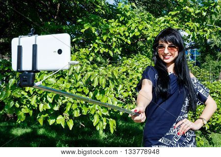 Pretty girl brunette with long hair makes selfie photos using a mobile phone and monopod selfie stick.