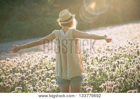 Enjoyment - free happy woman enjoying sunset. Beautiful woman embracing the golden sunshine glow of sunset with arms outspread enjoying peace, serenity in nature