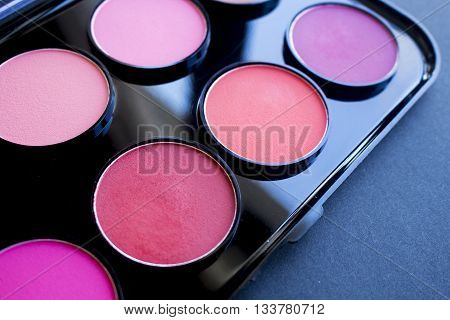 Colorful blush, shadow set on black background. Dry textured palette of professional cosmetics.