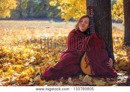 Young beautiful woman sitting with guitar under the tree on fallen leaves in autumn park wrapped in a shawl