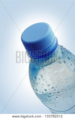 Water drops on a plastic bottle. The plastic bottle is located under an inclination. The bottle is closed by a cover. Vignette. Indoors. Vertical format. Color. Photo.