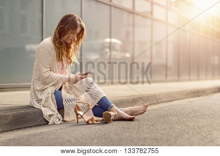 Attractive Woman Sitting On The Kerb Of A Street