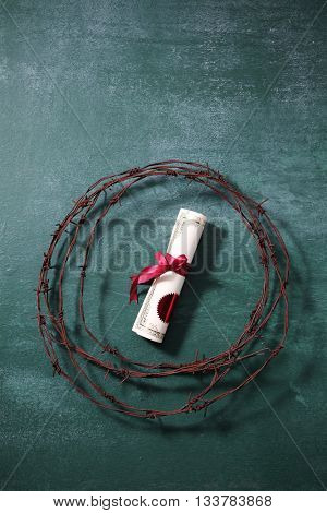 certificate with ribbon surrounded by barbwire