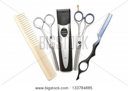Hairdressing industry. Professional hairdressing tools. Comb scissor clippers and hair trimmer isolated on white background