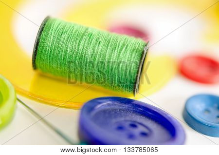 Sewing kit on the white background. Macro shot. Colorful set consisting of buttons pins soap and bobbins.