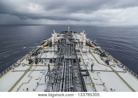 Oil products tanker underway in the ocean under cloudy sky.