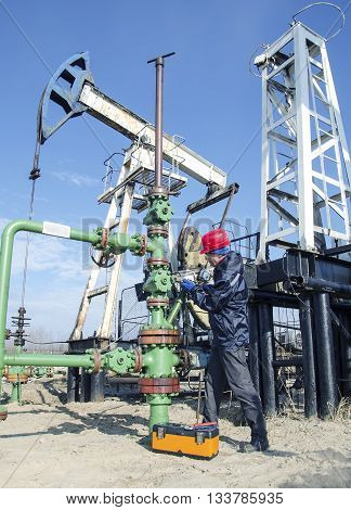 Worker reparing wellhead with the wrench in the oilfield. Tool box foreground pumpjack background. Oil and gas concept.
