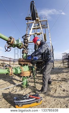Worker reparing wellhead with the wrench in the oilfield. Tool box foreground pumpjack background. Oil and gas concept. Fish eye shot.