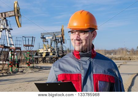 Worker wearing orange helmet in the oilfield. Pumpjack background. Oil and gas concept.