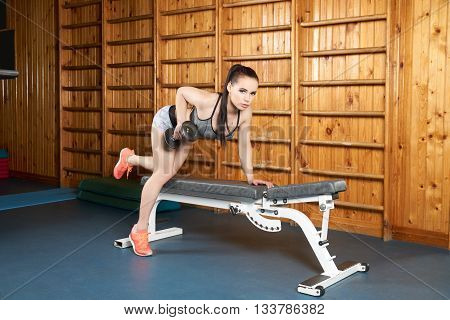 Beautiful young body builder doing exercises with dumbbells near wall bars in the gym