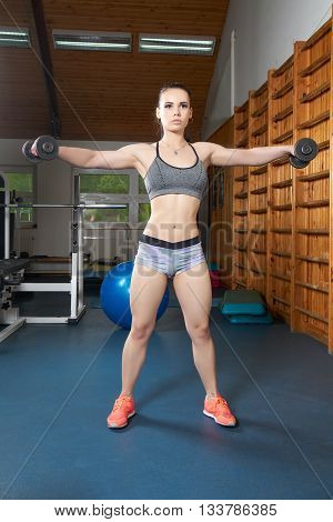 Beautiful young body builder doing exercises with dumbbells in the gym