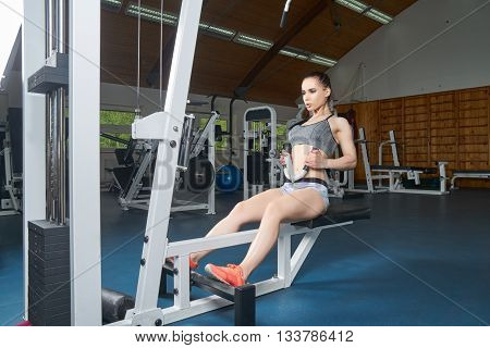 Beautiful young body builder doing muscles exercises on trainer in the gym