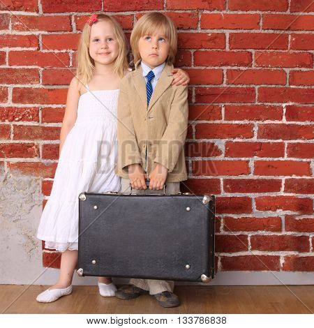 little boy in a suit and a beautiful girl in a white dress standing with a suitcase in his hand. Travel or relocation