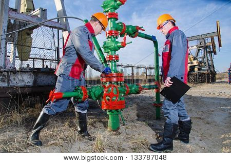 Workers in the oilfield one repairing wellhead with the wrench other supervising. Pumpjack and wellhead background. Oil and gas concept.
