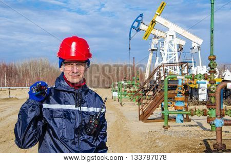 Portrait of man engineer in the oil field wearing red helmet and work clothes holding wrenches in his hand and radio in jacket pocket. Blurry pump jack and wellhead background. Oil and gas concept.