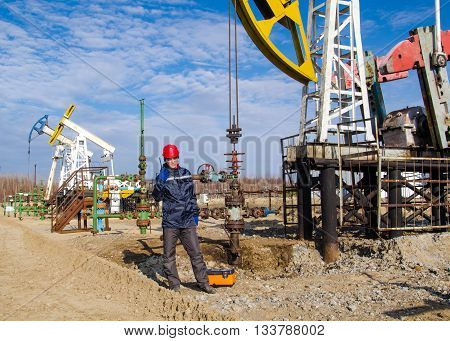 Man engineer in the oil field wearing red helmet and work clothes talking on the radio. Pump jack and wellhead background. Oil and gas concept.
