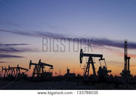 Pump jacks and derrick silhouette during sunset on the oilfield. Oil and gas concept.