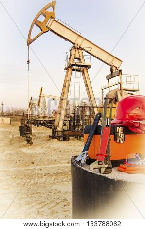 Tool box helmet and wrenches on the background of blurry pump jack. Oil and gas concept. Toned.