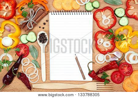 Vegetables spices and notepad for recipes on wooden table.