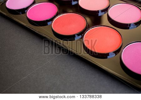 Colorful blush, shadow set on black background. Dry textured professional cosmetics.