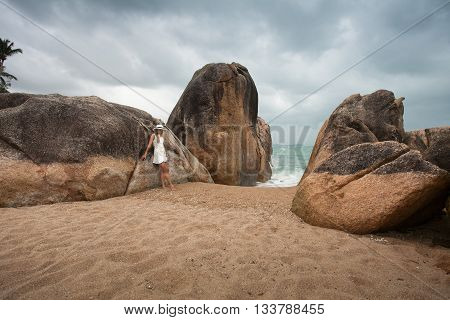 Lonely slender woman on a deserted beach on the background of large stones and a dark cloudy sky.