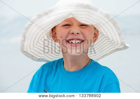 boy laughing in the women's white hat
