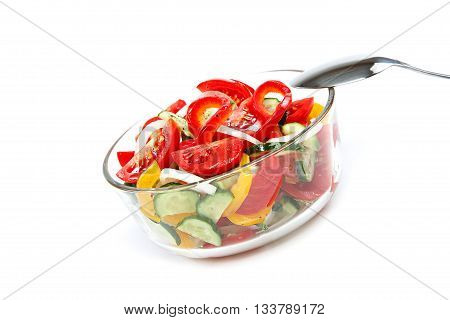 Fresh vegetable salad in a glass dish isolated on a white background.