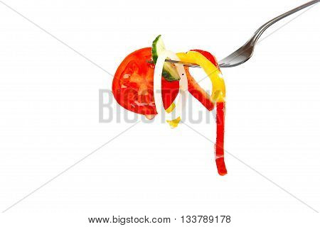 Slices of fresh vegetables in oil on a fork isolated on a white background.