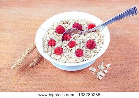 Fresh raspberries Oatmeal flakes on a wooden table. Healthy food.