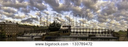 Prattville, Alabama, March 25, 2016: Panoramic view of the mill pond waterfall and Continental Eagle Gin building with dramatic cloud sky.
