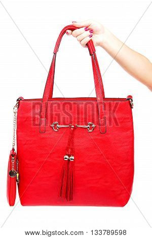 Red modern fashionable lady's bag in his hand isolated on white background.