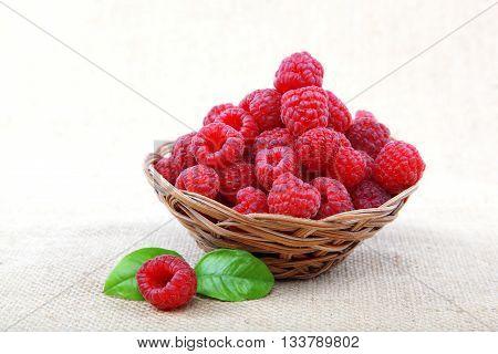 Raspberries in a basket on a homespun cloth.