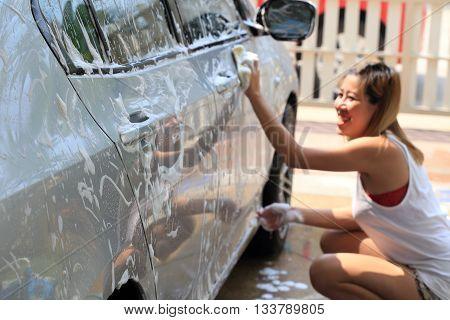car wash happy woman washing car in home