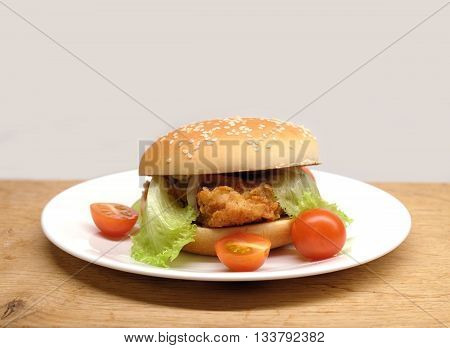 Fast food closeup. Appetizing homemade beef burger with salad and small tomatoes on white plate ready to eat front view isolated on beige
