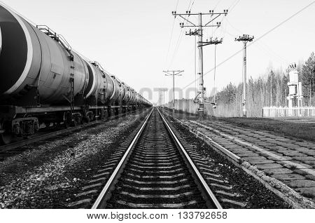 Train with oil tanks. Transportation of fuel on the railroad. Black and white shot.