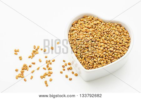 Fenugreek seeds in white bowl on white background