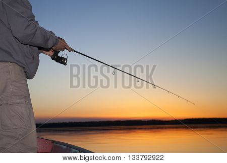 Man working a spinning real at sunset in Saskatchewan Canada
