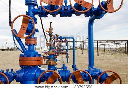 Group of wellheads. Oilfield with sand ground. Oil and gas concept.