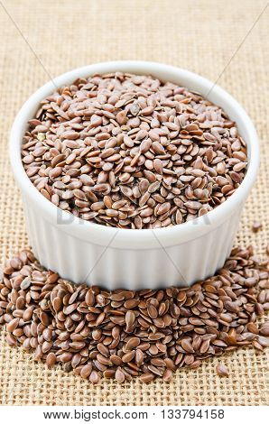 Brown flax seeds or linseeds in white bowl on sack background.