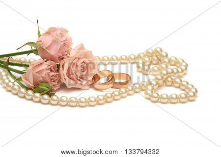 two golden rings pearls and flowers on white background