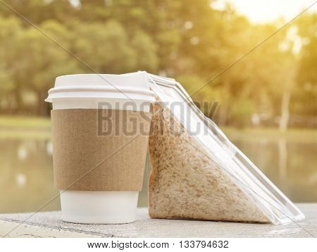 Hot paper cup of coffee and sandwich on wooden bench beside lake in the park under sunlight with warm / soft color tone (Breakfast time)