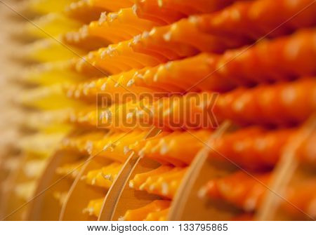 Colorful stick candles with orange and yellow tonality arranged in shelves and sorted by color in a candle shop.