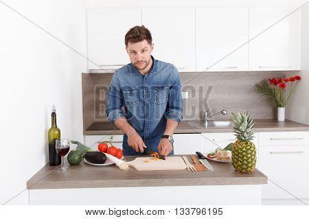 Handsome Young Man Cooking In A Modern Kitchen.