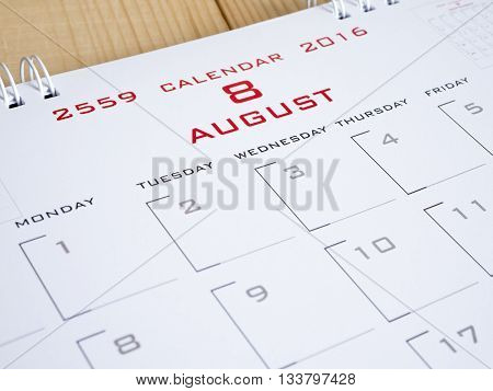 2016 August on calendar page desk calendar on wood background (Selective focus)