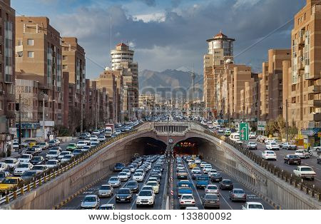 TEHRAN IRAN - FEBRUARY 19 2016: Heavy Traffic Congestion in and around Tohid Tunnel with Milad Tower and Alborz Mountains in Background. Tohid is the third longest urban tunnel in Middle East.